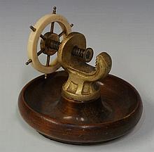 A ship's wheel nutcracker with ivorine wheel, dish
