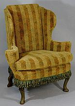 A George II style wingback armchair on green paint