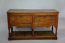 An oak dresser base the rectangular top above a fr