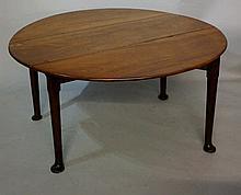 A George III mahogany oval drop leaf table on turn