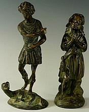 A bronze figure of a man standing upon stylised dr