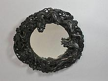 A Chinese hardwood circular mirror with bevelled
