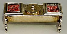 A silver trough shaped stamp case, two franked red penny stamps within glas