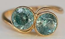 A 9ct gold blue zircon crossover ring with pair of circular brilliants, rin