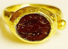 A Roman gold coloured metal ring, the hardstone intaglio carved with two fi