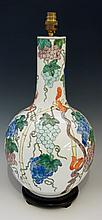 A porcelain lamp of baluster shape with tall neck decorated overall with vi