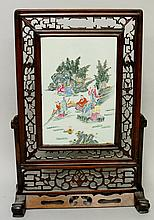 A Chinese famille rose screen, the porcelain panel painted with scholars wi