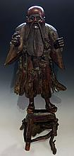 A Chinese rootwood and twig carving of Hotei, the figure with arms raised s