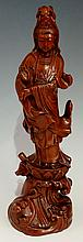 A Chinese hardwood carving of Guanyin, standing on a lotus and wave cast ba