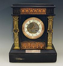 A Victorian black slate mantel clock of architectural form, the frieze inla