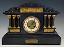 A Victorian black slate mantel clock of architectural form, domed top flute
