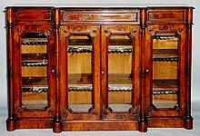 A Victorian breakfront mahogany bookcase, the top butterfly veneered with m