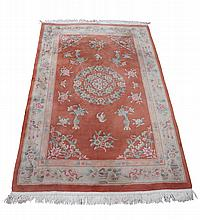 A Chinese rug, central circular floral medallion on salmon pink ground with