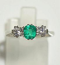 A ladies white gold emerald and diamond ring the oval emerald flanked by a