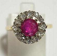 A ladies ruby and diamond ring the Burmese circular ruby claw set within a