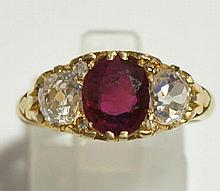 A ladies 18ct yellow gold ruby and diamond ring the oval ruby flanked by a