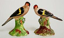 A pair of Derby birds, each perched on a floral encrusted green branch and