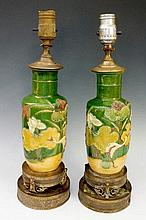 A pair of Chinese pottery lamps moulded in relief with flower heads, lily p