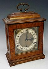 A walnut bracket clock in George II style the domed top with brass carrying