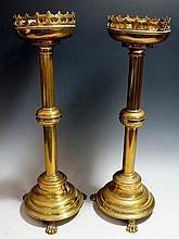A pair of Victorian brass candlesticks of Gothic form, the cylindrical nozz