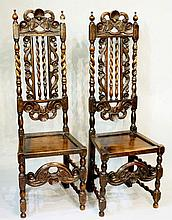 A pair of William and Mary style oak high back hall chairs the cresting rai