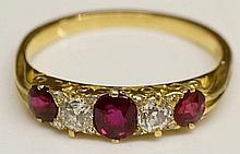 An 18ct ruby and diamond ring, the three oval rubies flanking a pair of circular diamond brilliants, rubies 0.81 carats, estimated total diamond weight 0.3 carats, ring size Q