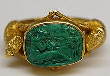 An 18ct gold ring, the oval malachite intaglio finely carved with a seated classical female holding a ewer, eagle cast shoulders, ring size S