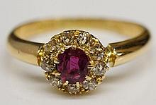 An 18ct yellow gold, ruby and diamond ring, the central oval ruby within a border of nine small diamond brilliants, ring size O