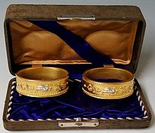 Louis Tiffany & Co. - a pair of gold and platinum bracelets with formal borders applied in gold and platinum with doves and scrolling flower heads and leafage, 6cm diameter, stamped LT & Co, boxed, 68gms For similar bracelets which are now in The