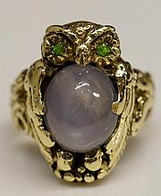 Walton & Co - a 14k gold star sapphire owl ring, realistically modelled with green gem set eyes and oval star sapphire cabochon, approx. 6.43 carats, foliate cast shoulders, stamped Walton & Co, ring size L/M