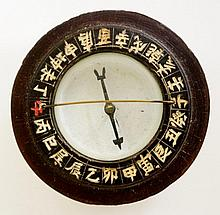 A 19th Century Chinese maritime compass the lift-off wooden lid engraved with a signature revealing a bezel with Chinese symbols, white ground with cut metal pointer, wooden case, 9cm diameter, 5.5cm high