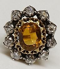 A Victorian 18ct yellow gold citrine and diamond ring, the oval cut citrine flanked by an open border of ten diamond brilliants, foliate pierced and engraved shoulders, marked, ring size L