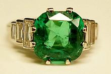 An emerald and diamond ring, the Columbian natural cushion shaped emerald flanked by step cut diamond shoulders, the emerald approx. 4.56 carats, together with an Anchor Gemalogical Laboratory Certificate number 20016366, dated 23rd May 2014,