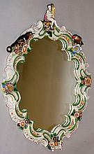 A Continental  polychrome decorated porcelain mirror,  the ornate floral en