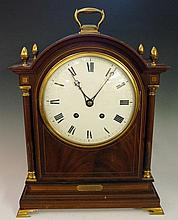 An Edwardian mahogany mantel clock in George III style the case inlaid overall with boxwood and ebony stringing, the domed top with four stylised acorn finials, white enamel dial with Roman numerals, twin winding holes, the eight day movement