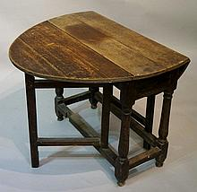 A late 17th Century oak oval gate leg table the oval top above tapered vasular columns joined by moulded stretchers, the gates plain, 104cm x 86cm oval, 68cm high (faults)