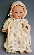 An Armand Marseille porcelain headed doll with closing eyes, composite arms and legs, composite limbs and body, back of head stamped A M Gremany 341./3K, clothed in knitted cream nightgown, jacket and bonnet, 29cm high, Circa 1930