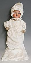 An Armand Marseille of Sonneberg and Koppelsdorf porcelain headed doll with closing eyes, synthetic hair, composite arms and legs, papier mache body, back of head stamped A M Koppelsdorf Gremany 1330 A7M, wearing white nightgown and bonnet, 52cm