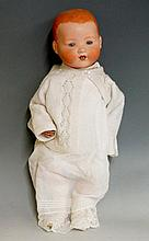 An Armand Marseille doll with closing eyes, back of head stamped A.M. Germany 351./6K, composite limbs and body, clothed in white nightgown with lace hem and hand knit cardigan, 52cm high, Circa 1930 (faults)
