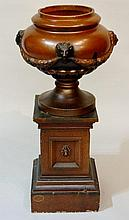 A Victorian salt glazed lobed pedestal urn the compressed globular body moulded in relief with lion mask, leafy drapes, circular foot, the square pedestal panelled with lion masks on a spreading square base, impressed T. Knowles, Darwen, 87cm high,