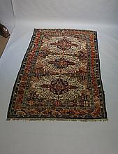 A Kuba rug the field worked with three blue and iron red barbed medallions