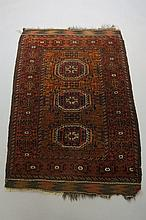 A Baluch rug worked with three octagonal medallions on a filled dark sand g