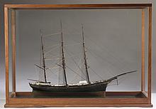 CASED MODEL OF A THREE-MASTED SHIP WITH GILDED EAGLE FIGUREHEAD.