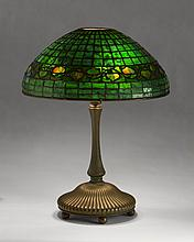 TIFFANY STUDIOS PATINATED-BRONZE LAMP BASE, NEW YORK, 1899-1920, FITTED WITH A LEADED GLASS 'ACORN BORDER' SHADE.