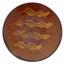 PENNSYLVANIA SLIP-DECORATED REDWARE DISH, MID-NINETEENTH CENTURY.