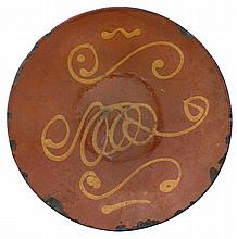NEW ENGLAND SLIP-DECORATED REDWARE DISH, POSSIBLY NORFOLK, CONNECTICUT, EARLY NINETEENTH CENTURY.