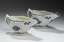 NEAR PAIR OF LOWESTOFT PORCELAIN BLUE AND WHITE PRINTED SAUCEBOATS, RELIEF-MOLDED IN THE MANNER OF JAMES HUGHES, 1775-85.