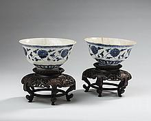 PAIR OF CHINESE PORCELAIN BLUE AND WHITE CRACKLE GLAZE BOWLS PAINTED WITH LOTUS BLOOMS AND VINES, WITH PIERCE-CARVED HARDWOOD STANDS.