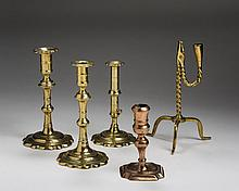 FOUR GEORGE II/III BRASS AND COPPER CANDLESTICKS AND A RUSH LIGHT.