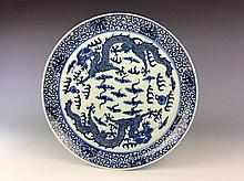 Chinese export blue and white porcelain plate painted with dragons and clouds.